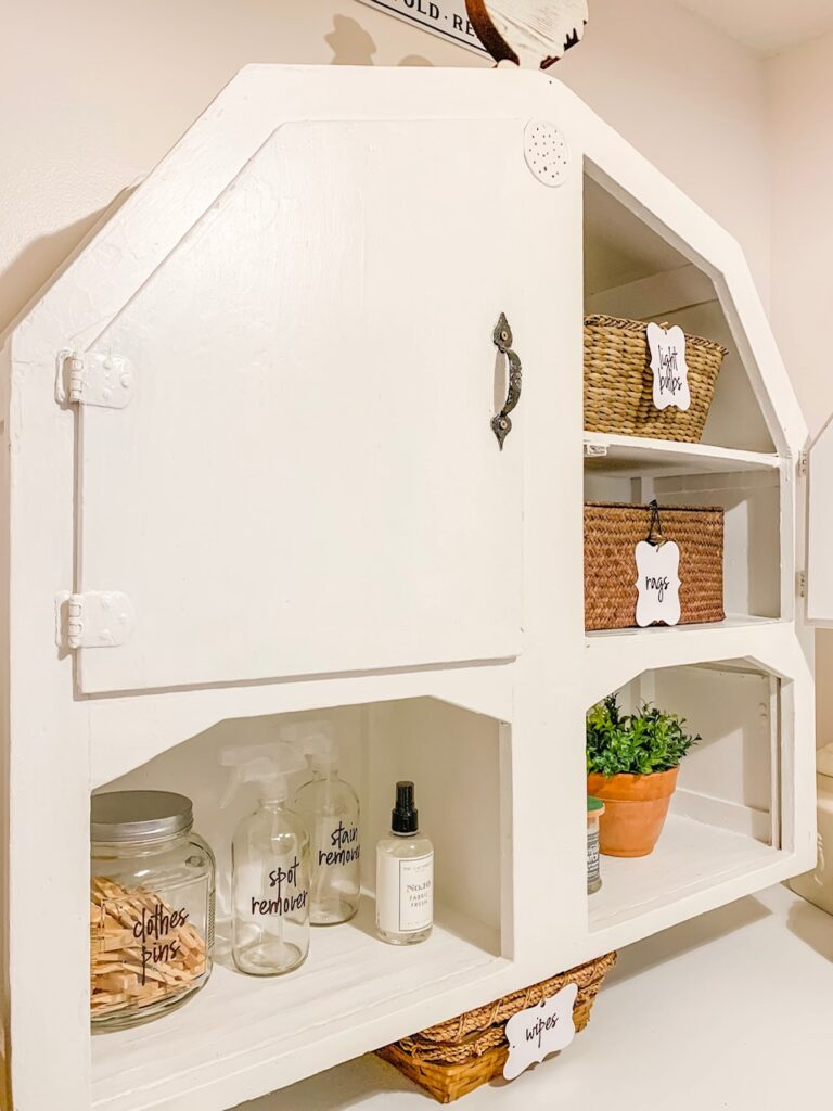 white painted primitive wood wall cabinet to hold supplies in laundry room makeover