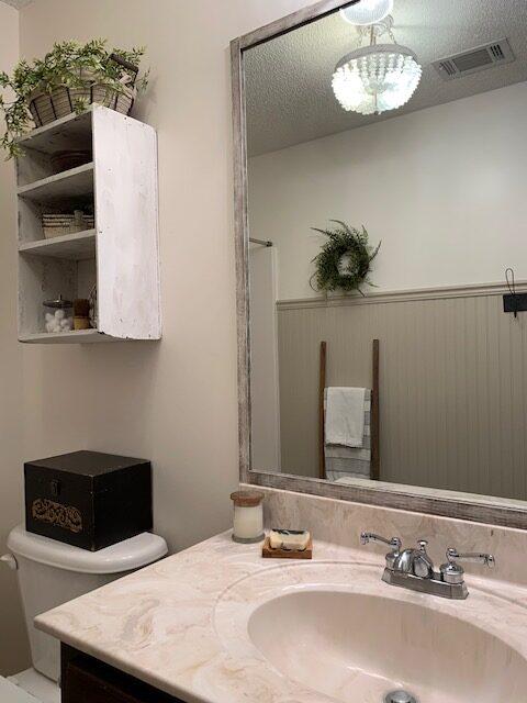 a diy tutorial for framing a bathroom wall mirror