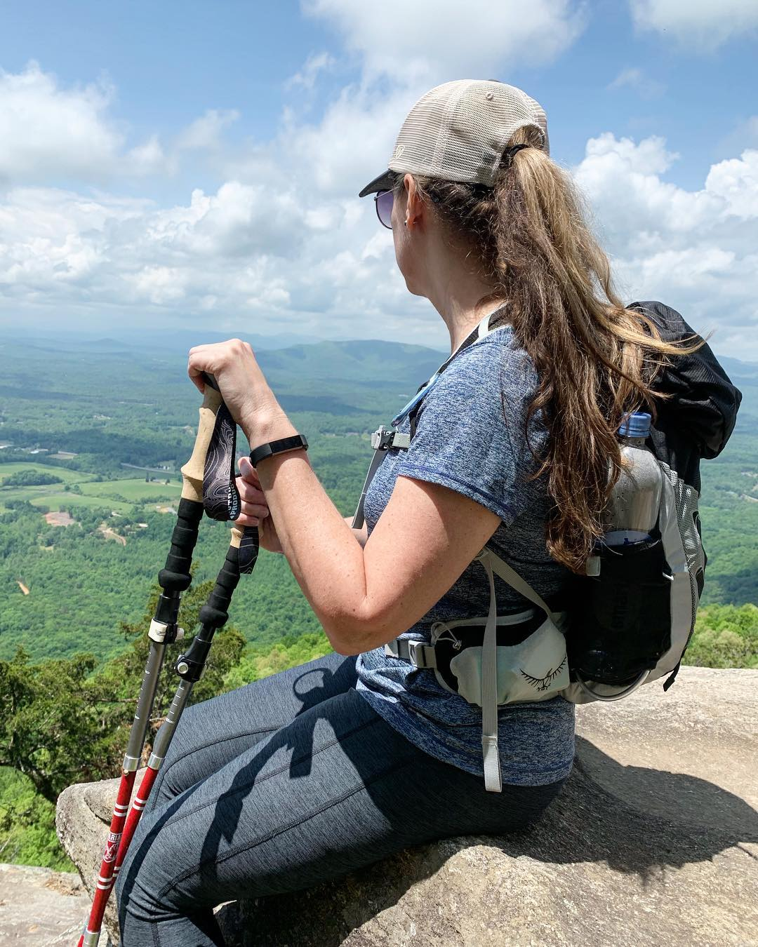 woman sitting on a mountain top after a hard climb
