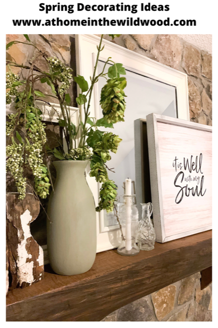 A cottage style mantel decorated for spring with faux greenery, a mirror, a picture, and empty frames