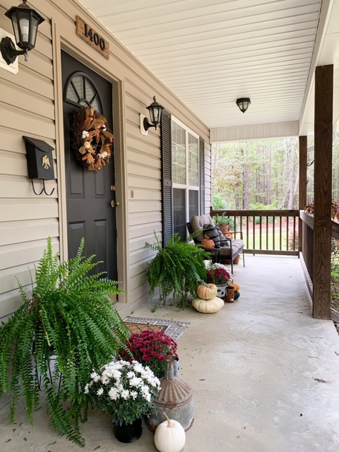 A front porch decorated for fall showcasing a black front door painted with fusion mineral paint