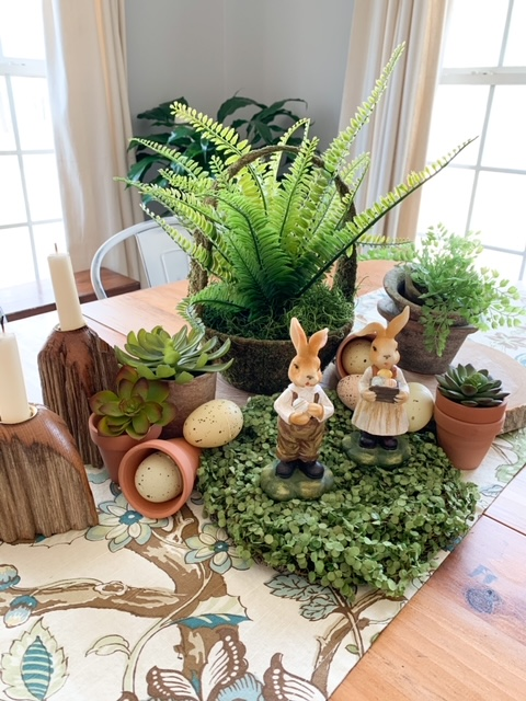A spring table centerpiece made from faux greenery, wood rounds, wood candlesticks, faux eggs, and bunnies