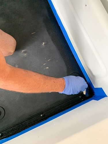 using a foam brush or other inexpensive brush, paint the corners of the bed before rolling on the paint