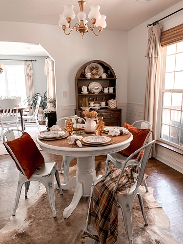 A cozy dining room space decorated for an early fall dinner