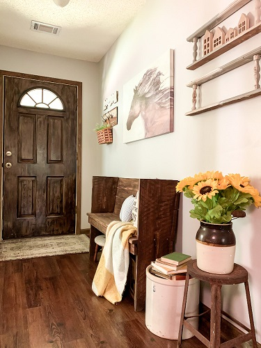a front foyer is decorated for a early fall with sunflowers, a vintage pew, and art work