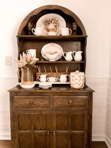A vintage hutch in a dining room decorated with ironstone and other thrifted finds