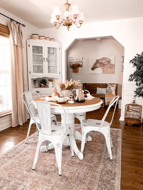 A cottage dining room decorated for fall with a neutral color scheme