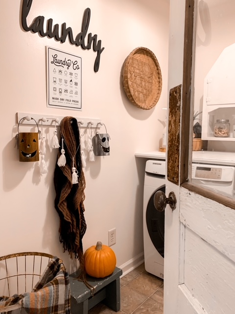 a farmhouse style laundry room with fall decorations such as cute Halloween lanterns, a yarn ghost garland, and a faux pumpkin