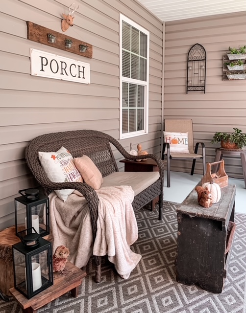 screened in back porch styled for the fall season with wicker furniture, lanterns, and cozy throw and pillows